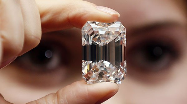 A staff member holds a 100-carat perfect diamond in a classic emerald-cut at Sotheby's auction house in central London