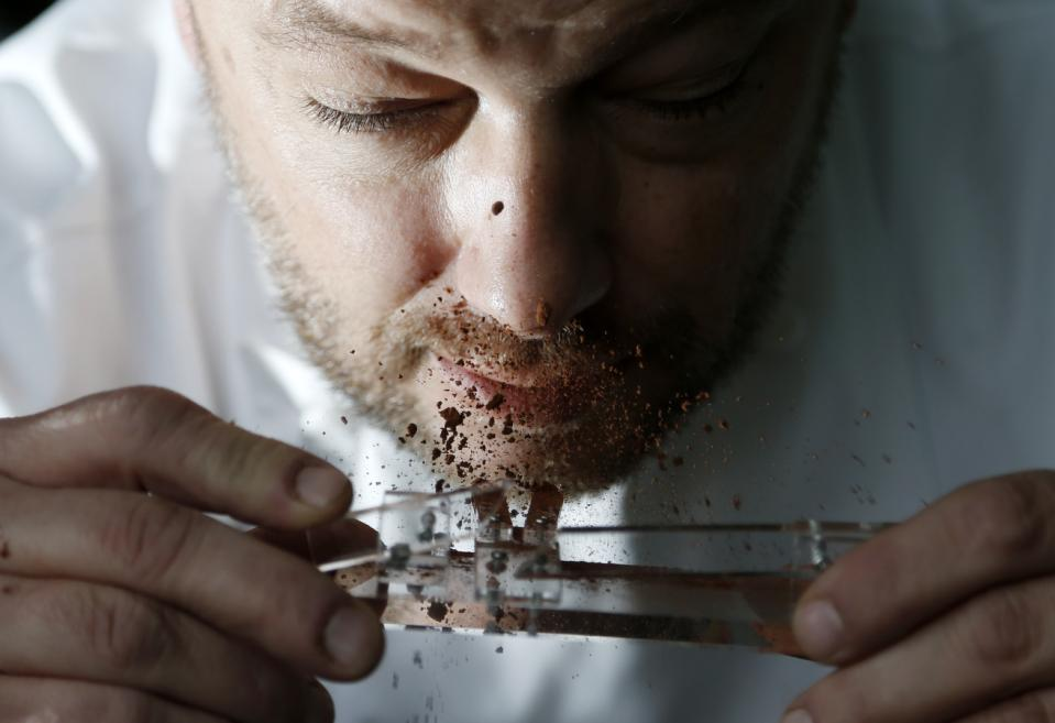 Belgian chocolatier Persoone snorts cocoa powder off his Chocolate Shooter in his factory in Bruges